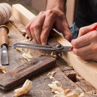 schrijnwerker bewerkt hout en tekent de maten af